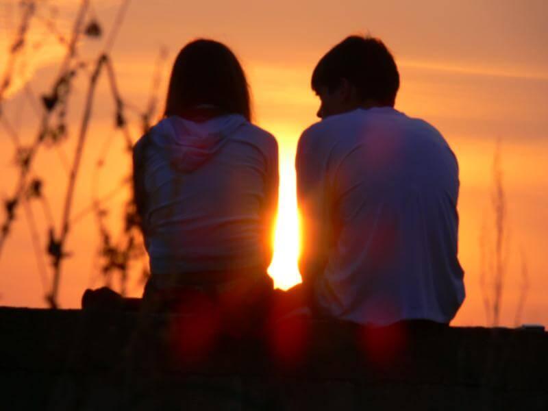 парень и девушка сидят при закате солнца