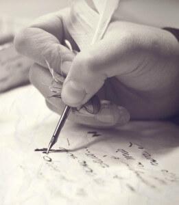 Человек пишет пером на бумаге