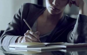 девушка пишет на листке бумаги карандашом и самостоятельно изучает проблему