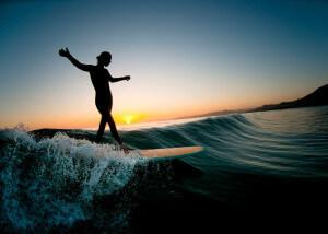 уверенный серфер девушка на волне с закатом солнца на фоне