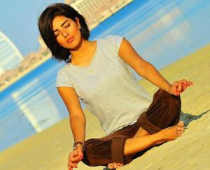 Девушка медитирует на пляже, чтобы избавиться от ненужных мыслей