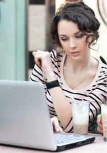 Красивая девушка сидит за ноутбуком и ведет знакомства в контакте