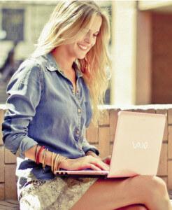 Красивая девушка с ноутбуком сидит в интернете и собирается написать подруге