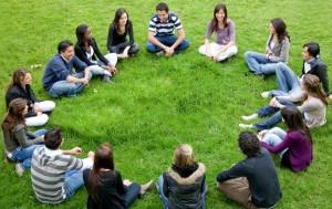 Круг людей сидит на газоне